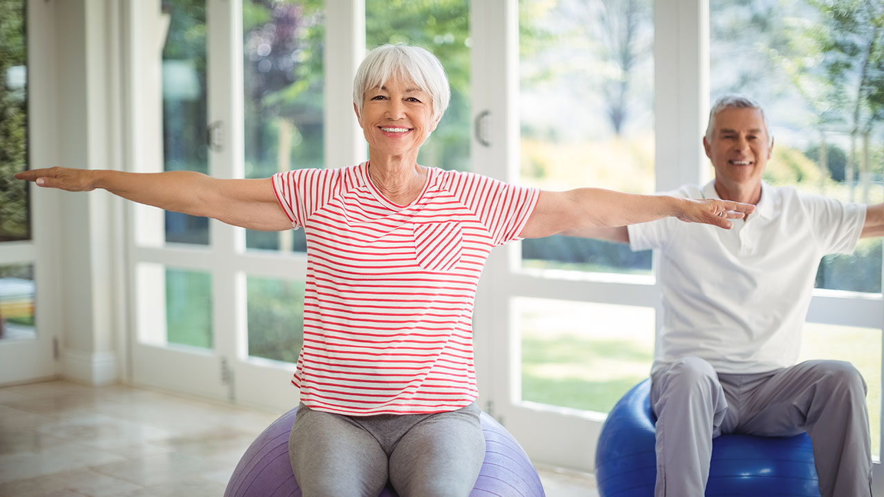 Two Seniors sit on medicine balls with their arms stretched out while smiling